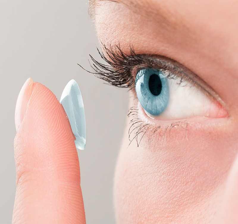 Woman inserting a contact lens in eye