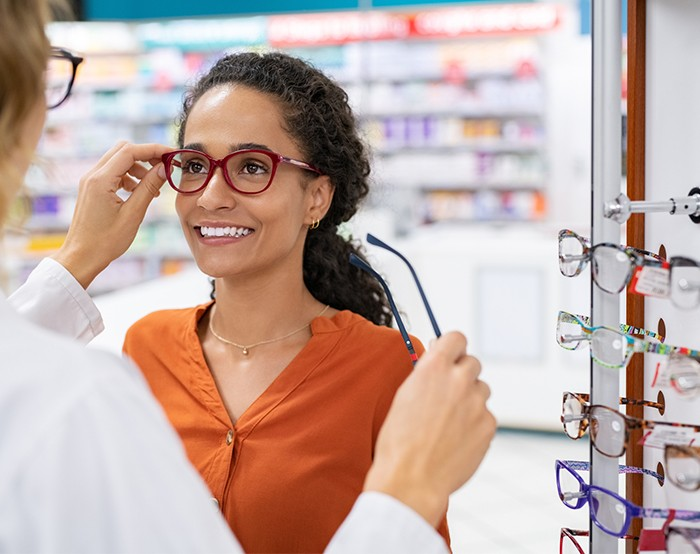 Female doctor helping woman try one pair of glasses