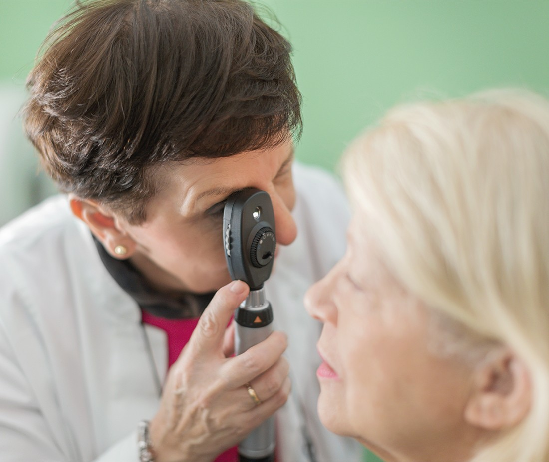 Senior female doctor doing eye test with female patient