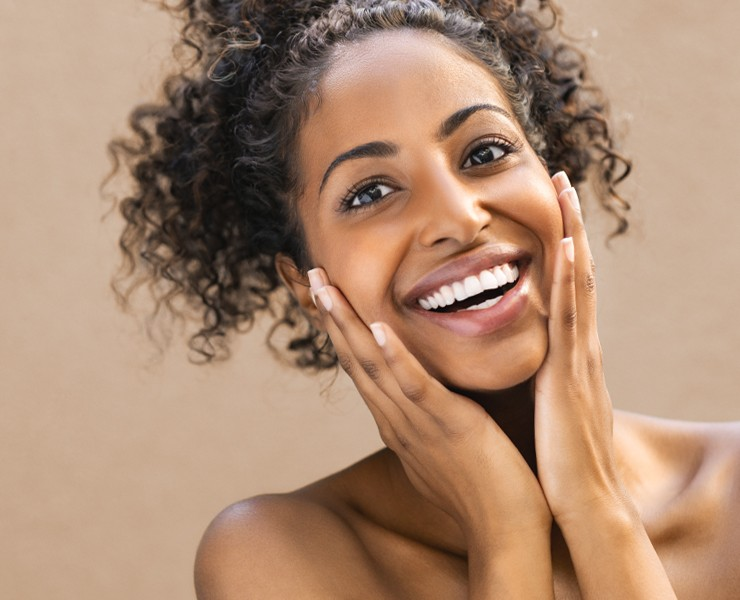 Woman with hands around face smiling, smooth skin