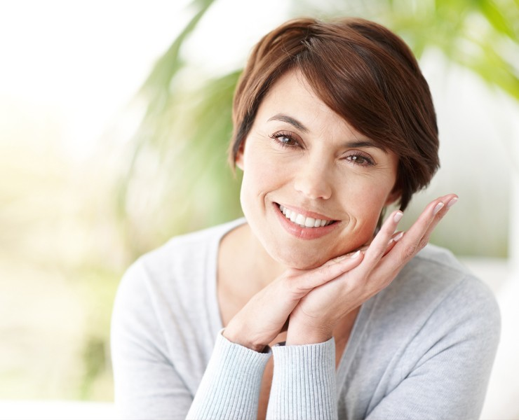 Older woman smiling with hands close to face